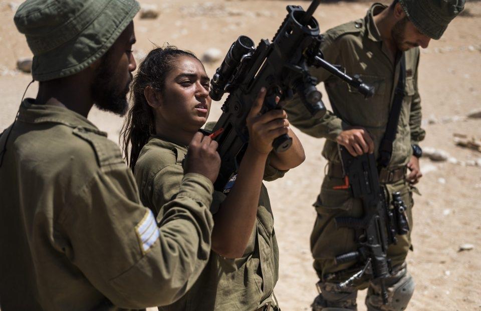 Các binh sĩ nam đang hỗ trợ một binh sĩ nữ tập luyện.