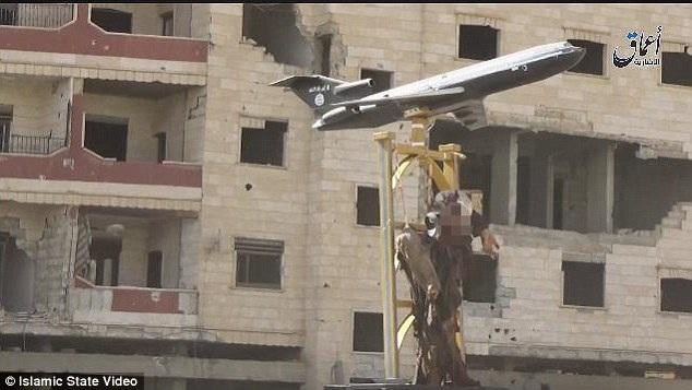 Xác phi công bị đóng đinh và treo bên dưới mô hình máy bay ngoài đường phố (Ảnh: Dailymail)