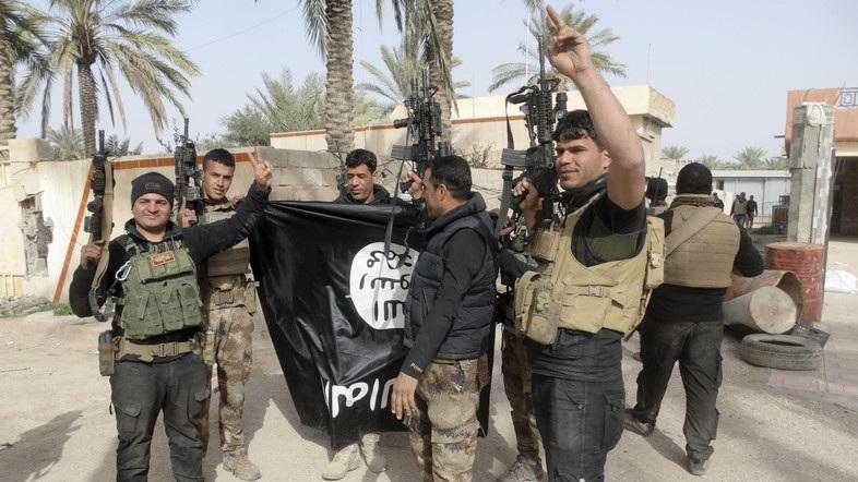 Lực lượng an ninh Iraq cầm cờ của IS ăn mừng sau khi giành được thành phố Ramadi từ tay IS (Ảnh: Alarabiya)