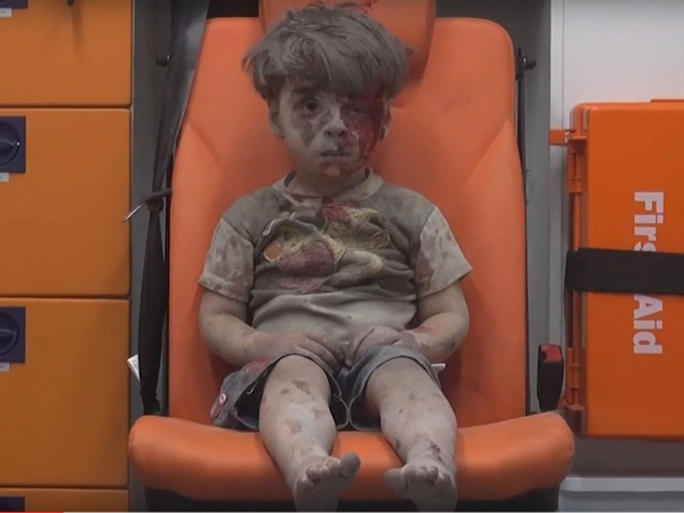 Omran Daqneesh ngồi thất thần trên xe cứu thương sau khi được giải cứu khỏi một ngôi nhà bị sập do không kích ở Syria. (Ảnh: Independent)