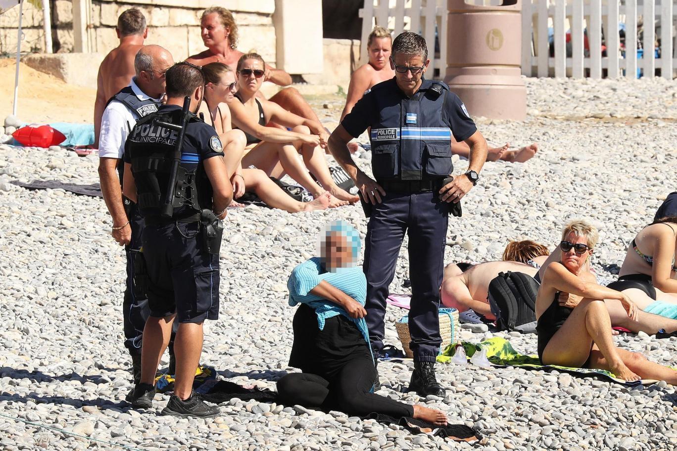 Cảnh sát Pháp yêu cầu một phụ nữ cởi bỏ trang phục burkini trên bãi biển ở thành phố Nice, Pháp (Ảnh: Independent)