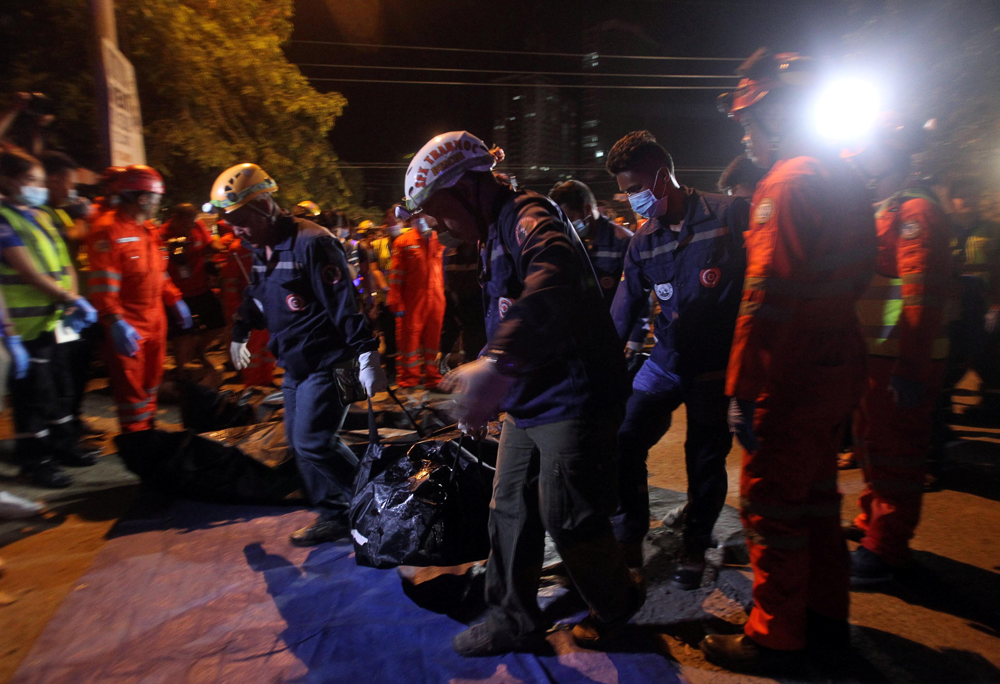 Lực lượng cứu hộ đưa thi thể nạn nhân ra ngoài.