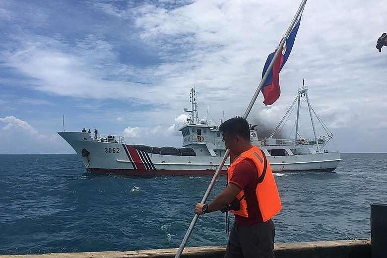 Một nhà hoạt động Philippines chuẩn bị đi tàu lên cắm cờ Philippines tại bãi cạn Scarborough trong khi bị tàu của cảnh sát biển Trung Quốc áp sát bên cạnh (Ảnh: Straitstimes)