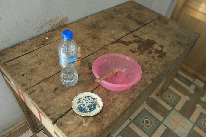 Trên bàn là bát cơm đã ăn hết và ít muối trắng cùng một chai nước.