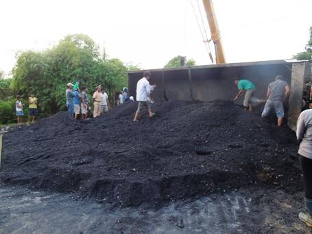 Người dân phụ giúp tài xế xe tải xúc than ra khỏi thùng xe