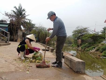 Thương binh 1/4 Nguyễn Văn Thống cùng vợ quét rác, dọn dẹp vệ sinh ở chợ trung tâm xã Nhân Trạch.