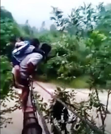 Cảnh tượng hãi hùng người đàn ông cõng học sinh qua con suối dữ đến trường (Ảnh cắt lừ clip)