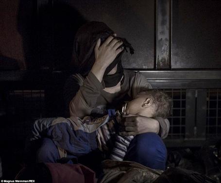 Cậu bé Sham 1 tuổi đang nằm ngủ trong vòng tay mẹ ở biên giới giữa Áo và Serbia.