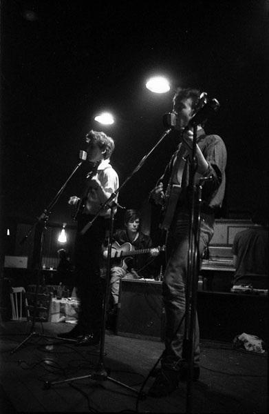 Sutcliffe chơi bass phía sau John Lennon và George Harrison tại một câu lạc bộ ở Hamburg.
