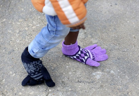 Ngày 16/2: Một em nhỏ người Châu Phi đã biến hai chiếc găng tay trở thành đôi giày sau khi con tàu vận chuyển người di cư từ Bắc Phi cập cảng ở đảo Sicily, Ý.