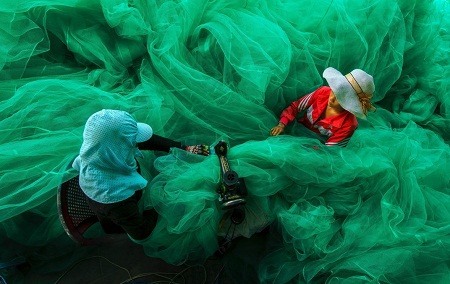 Hạng mục Con người: Những phụ nữ sống trong một làng chài nhỏ gần vịnh Vĩnh Hy, Ninh Thuận. Họ đang ngồi may lưới đánh cá trong khi chồng họ đang ra khơi. (Ảnh: Phạm Tỵ)
