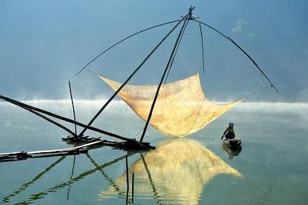 Hạng mục Du lịch: Một ngư dân đang kiểm tra vó trong buổi sáng sớm trên hồ Tuyền Lâm, Đà Lạt. Buổi đêm, ngư dân thường hạ vó xuống và bật đèn sáng ở phía trên vó, nhằm thu hút cá, tôm bơi vào. (Ảnh: Lý Hoàng Long)