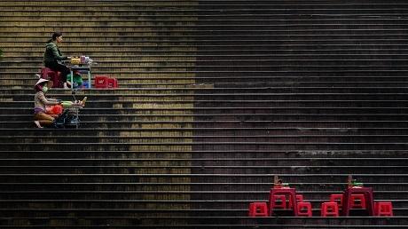 """Bức """"Người bán hàng rong trên những bậc thang"""" của Quang Trần. Bức ảnh được chụp ở thành phố Đà Lạt ghi lại cảnh những người phụ nữ đang bán hàng trên những bậc thang sau một cơn mưa nặng hạt. Khi thực hiện bức ảnh này, Quang Trần đang đi vòng quanh thành phố để xem người dân nơi đây kiếm sống như thế nào và đã tình cờ bắt gặp khung cảnh này."""