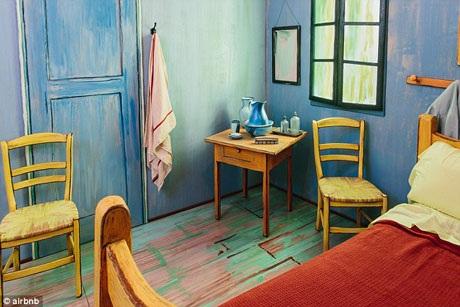 Chiếc giường đôi với chiếc chăn màu đỏ nằm ở một góc phòng giống như những gì được khắc họa trong tranh.