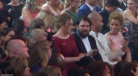Hình ảnh Adele thất thần khi trở về hàng ghế khán giả. Người đàn ông mặc vest ngồi bên cạnh cô chính là bạn trai lâu năm của cô - Simon Konecki.