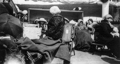 Những người sống sót ngồi gần lại với nhau để truyền hơi ấm trên sàn tàu Carpathia.