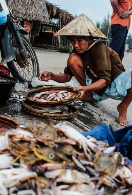 """Bức """"Đi thăm chợ cá"""" - Shane Hayes (Úc). Vào buổi sáng sớm, những người phụ nữ đội nón lá đi ra chợ để mua thức ăn tươi, về chuẩn bị bữa cơm cho gia đình. Người phụ nữ trong ảnh đang ngồi bên một sạp bán cá ven đường trong khu chợ cóc. Làng chài bé nhỏ này nằm ở gần Hội An."""