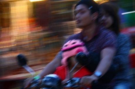 """Bức """"Đi xe máy"""" - Monique Brasil (Brazil). Bức ảnh này được chụp ở Hà Nội, đối với nhiếp ảnh gia Monique, đây là bức ảnh gói gọn những dòng chảy xe cộ huyên náo trên đường phố ở các thành phố lớn tại Việt Nam. Monique chia sẻ kinh nghiệm rằng bạn cần phải thật dũng cảm để có thể sang đường và đứng vào giữa dòng chảy xe cộ đông đúc. Mỗi một lần sang đường, Monique đều thấy đó là một thử thách thực sự."""