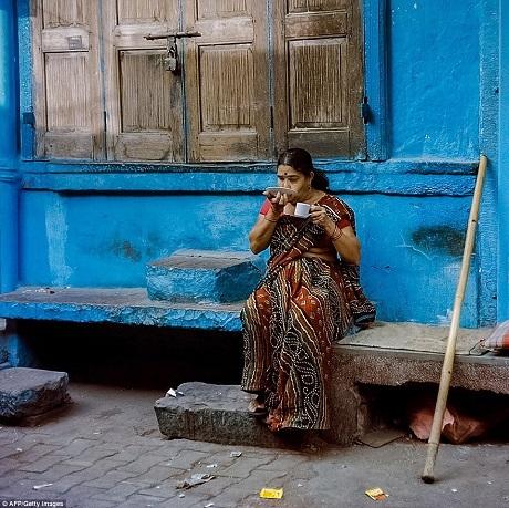 Người phụ nữ đang uống trà bên hiên nhà.