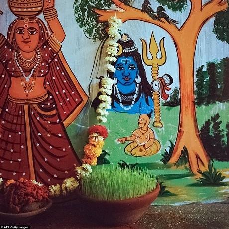 Hoa và đồ lễ được đặt trước một bức phù điêu khắc họa vị thần Shiva của đạo Hindu. Nơi này nằm ở bên trong một sân đền.