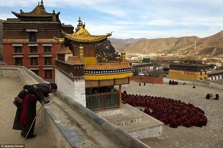 Một khách hành hương dừng lại cầu khấn, phía xa là những nhà sư đang tập trung bên ngoài gian thờ chính ở tu viện Labrang, Cam Túc, Trung Quốc. Tu viện này được dựng lên từ năm 1709, Labrang đã từng là nơi tu hành của hơn 4.000 nhà sư, hiện giờ có khoảng 1.500 nhà sư lưu lại nơi này.