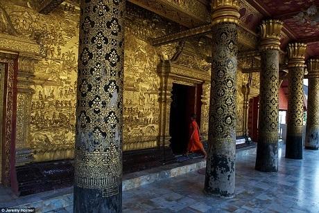Một chú tiểu bước vào ngôi đền Phật giáo Wat Mai ở Luang Prabang, Lào. Trong ảnh là một lối vào dát vàng được trang trí cầu kỳ, tỉ mỉ, và được bê đỡ bằng các hàng cột lớn.