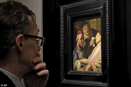 """Một vị khách chiêm ngưỡng bức tranh vừa mới được tìm thấy lại của Rembrandt. Bức tranh này vốn được đặt tên là """"Bệnh nhân bất tỉnh (Khứu giác)""""."""