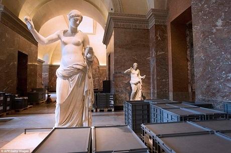 Những chiếc thùng nhựa chứa các tác phẩm nghệ thuật ở bảo tàng Louvre được đặt xen kẽ giữa các bức tượng bên trong một phòng trưng bày.