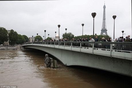Những du khách không thể vào thăm các viện bảo tàng và các điểm đến nổi danh tại Paris đành dừng chân bên cầu để chụp cảnh nước ngập.