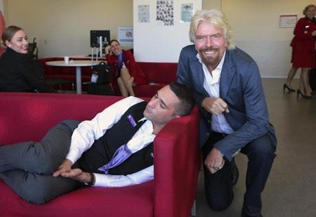 Hình ảnh tỉ phú Richard Branson xuất hiện thân thiện bên cậu nhân viên đang tranh thủ ngủ. Bức ảnh được chụp trong chuyến thăm của ông Branson dành cho các nhân viên làm việc cho hãng bay Virgin Australia.