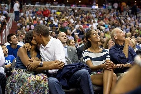 """Ông Obama đưa gia đình đi xem thi đấu thể thao, trong thời gian nghỉ giữa giờ, khi """"Kiss Cam"""" hướng đến vợ chồng ông, ông đã quay sang hôn vợ rất tự nhiên, đem lại cho sân vận động một khoảnh khắc ngọt ngào ấn tượng."""