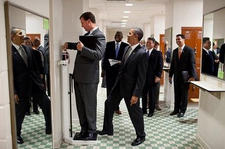 Ông Obama đặt chân của mình lên cân trong khi một người nhân viên đang tranh thủ kiểm tra cân nặng. Trò đùa của ông đã được nhiếp ảnh gia nhanh chóng ghi lại. Bức ảnh này cũng giống như rất nhiều bức ảnh khác xuất hiện ở đây đã từng gây sốt trên các mặt báo, giúp người ta hiểu hơn về cá tính và cuộc sống thường nhật của ông Obama.