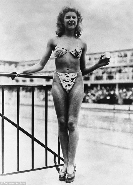 """Vũ nữ thoát y Michele Bernardini (ảnh) là người duy nhất nhận lời mời chụp hình với bikini của nhà thiết kế Louis Réard. Bức ảnh được chụp vào ngày 5/7/1946. Bộ đồ bơi được nhấn mạnh là """"nhỏ xíu"""" tới mức có thể nhét vừa chiếc hộp mà Michele đang cầm trên tay."""