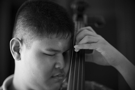 Cậu thiếu niên Kritsada Thanyawanichapong đang luyện tập chơi cello trước một buổi luyện tập của cả dàn nhạc tại ngôi trường dành cho trẻ khiếm thị ở thành phố Lopburi, Thái Lan. Ban nhạc Thai Blind Orchestra gồm những thanh thiếu niên khiếm thị có niềm đam mê với âm nhạc, ở độ tuổi từ 9-18 tuổi.