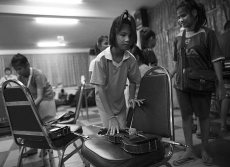 Cô bé Tanakarn Rungransri đang chuẩn bị luyện tập với cây đàn violin. Xung quanh em là những thành viên khác trong ban nhạc.