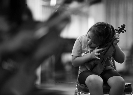 """Một cô bé khiếm thị có tên Cholticha Iamvijit, 10 tuổi, vừa mới gia nhập dàn nhạc. Cô bé đang """"thẩm âm"""" cây vĩ cầm của mình."""
