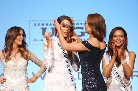 Vương miện đã rơi khỏi đầu Tân Hoa hậu khi cô vừa giơ tay lên vẫy chào trong niềm phấn khích. May mắn, người đẹp tiền nhiệm (váy đen) đã đỡ được vương miện.