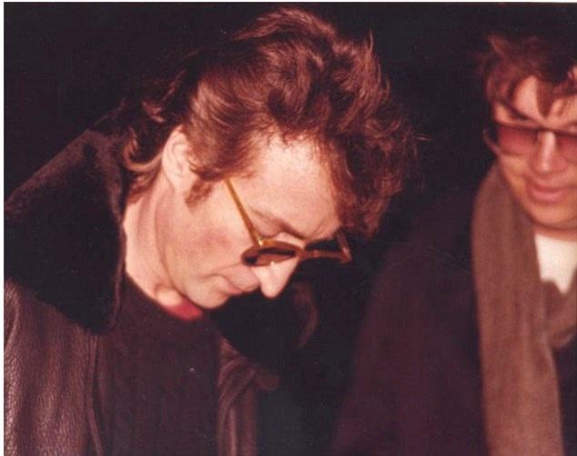 """Nam ca sĩ huyền thoại John Lennon đang ký tặng lên bìa đĩa album """"Double Fantasy"""" cho Mark Chapman bên ngoài tòa nhà chung cư nơi ông sinh sống. ngay sau đó, Chapman sẽ nã súng cướp đi tính mạng của nam ca sĩ nổi tiếng thế giới."""
