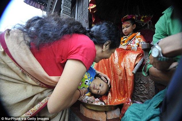 Hai mẹ con người phụ nữ đang hành lễ trước nữ thần sống Kumari của thành phố Patan.