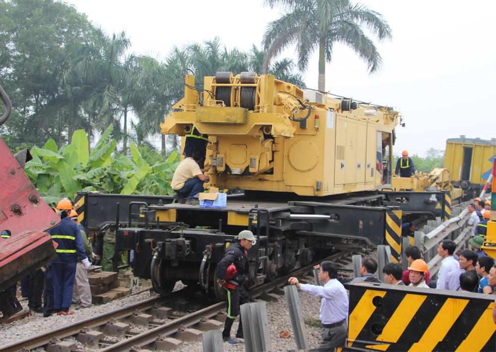 Điều động nhiều máy móc hạng nặng đến hiện trường để giải cứu đầu máy tàu hỏa và xe tải gặp nạn.