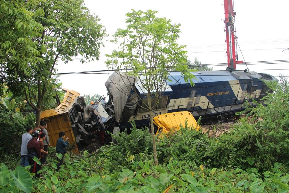 Xe tải và đầu máy tàu hỏa đều bị văng xuống vệ đường