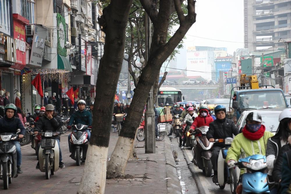 Phương tiện xe máy đi cả lên vỉa hè để thoát thân trên phố Chùa Bộc.