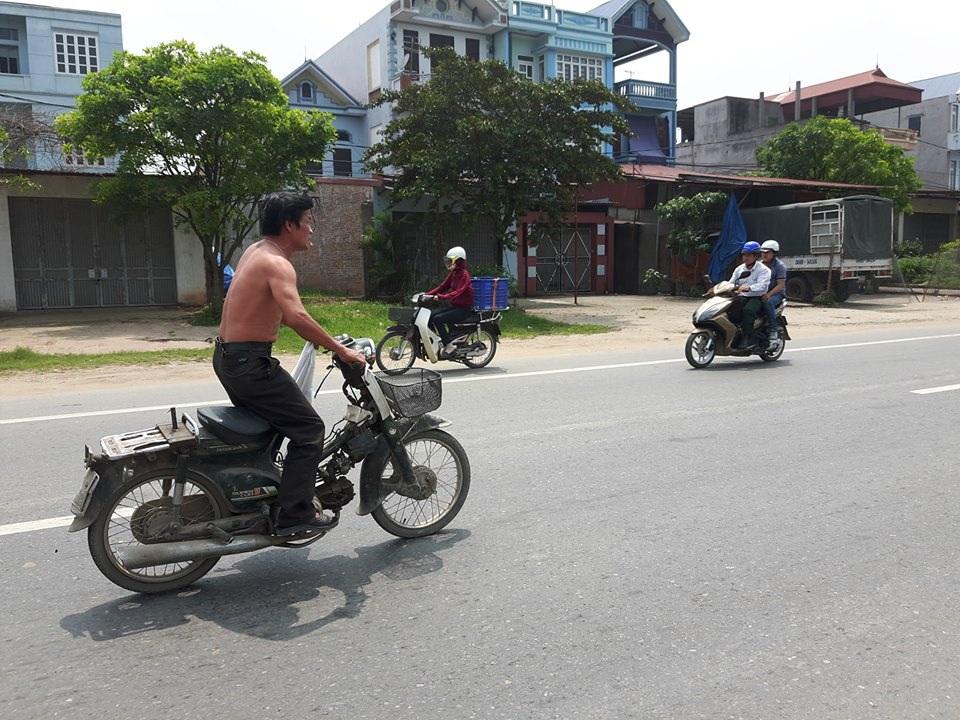 Người đàn ông đi xe máy trong tư thế này suốt quãng đường 5km khiến nhiều người đi đường bị phen hú vía (ảnh cắt từ clip)