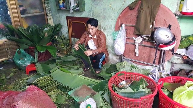 Vuốt sạch các lá chuối, lá ổi trước khi gói Tré
