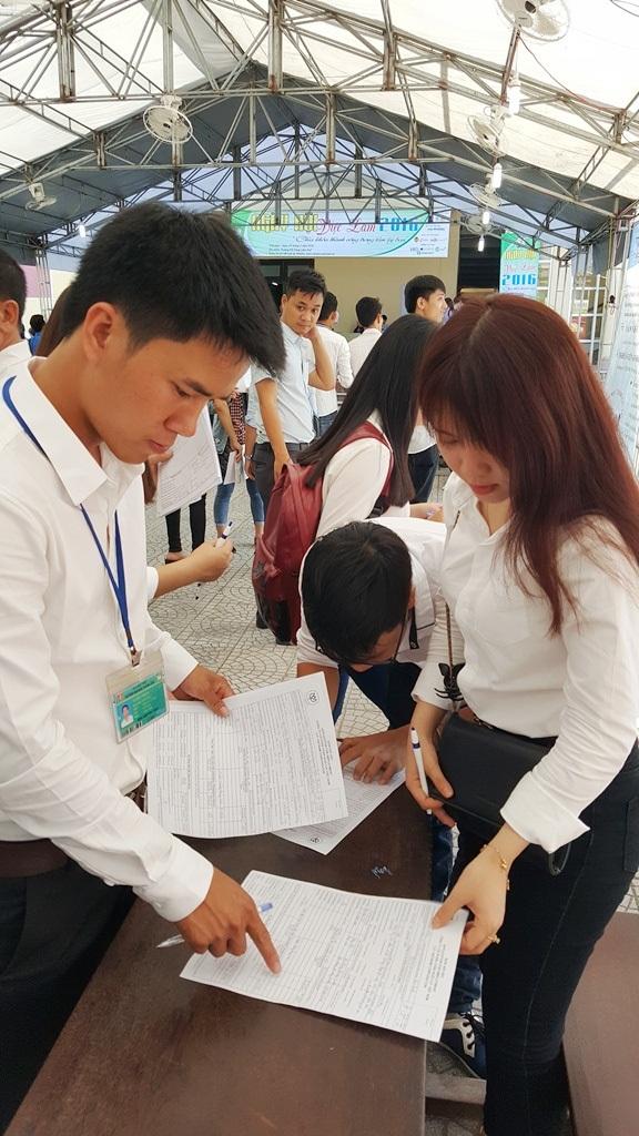 Một nhân viên từ công ty tuyển dụng xem xét hồ sơ của sinh viên nộp