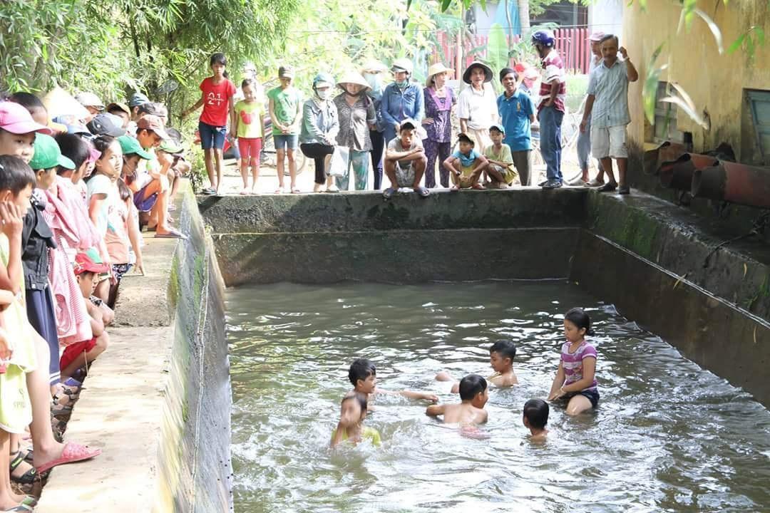 Nhiều phụ huynh thôn quê ra bể xả trạm bơm xem con mình tập bơi
