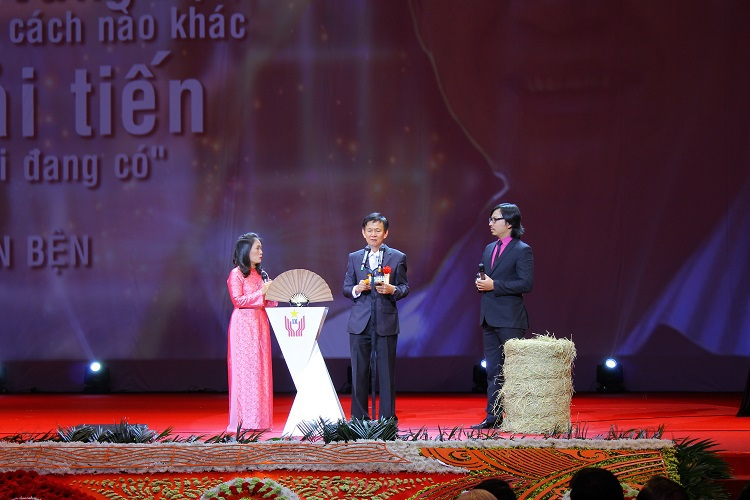 Ông Phan Tấn Bện bên cuộn rơm từ máy cuốn rơm của mình tại buổi lễ vinh danh cá nhân xuất sắc trong Đại hội Thi đua yêu nước toàn quốc lần IX