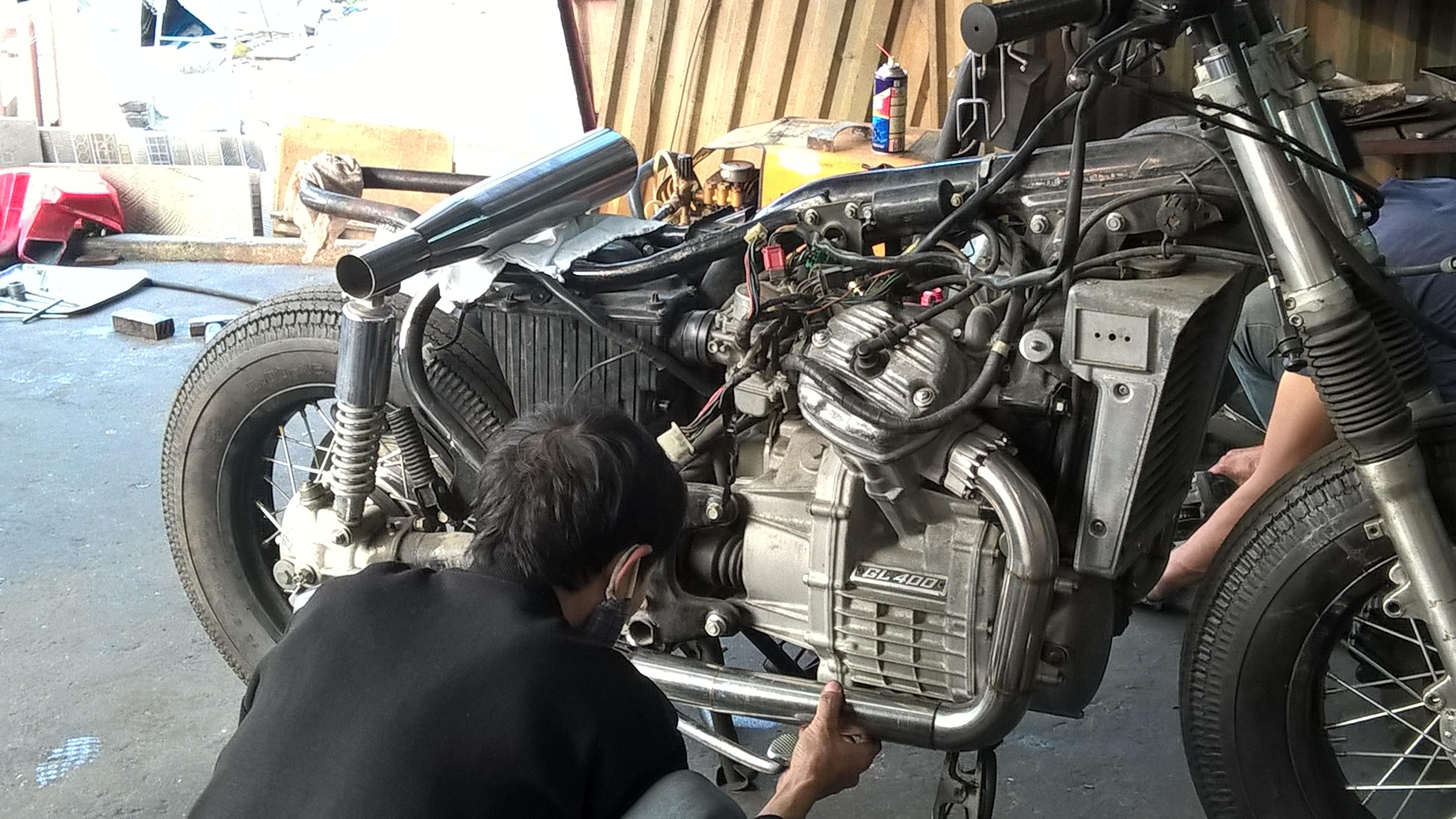 Thợ độ xe đang độ thay thế pô ống xả bằng hợp kim cho một chiếc xe độ phân khối lớn