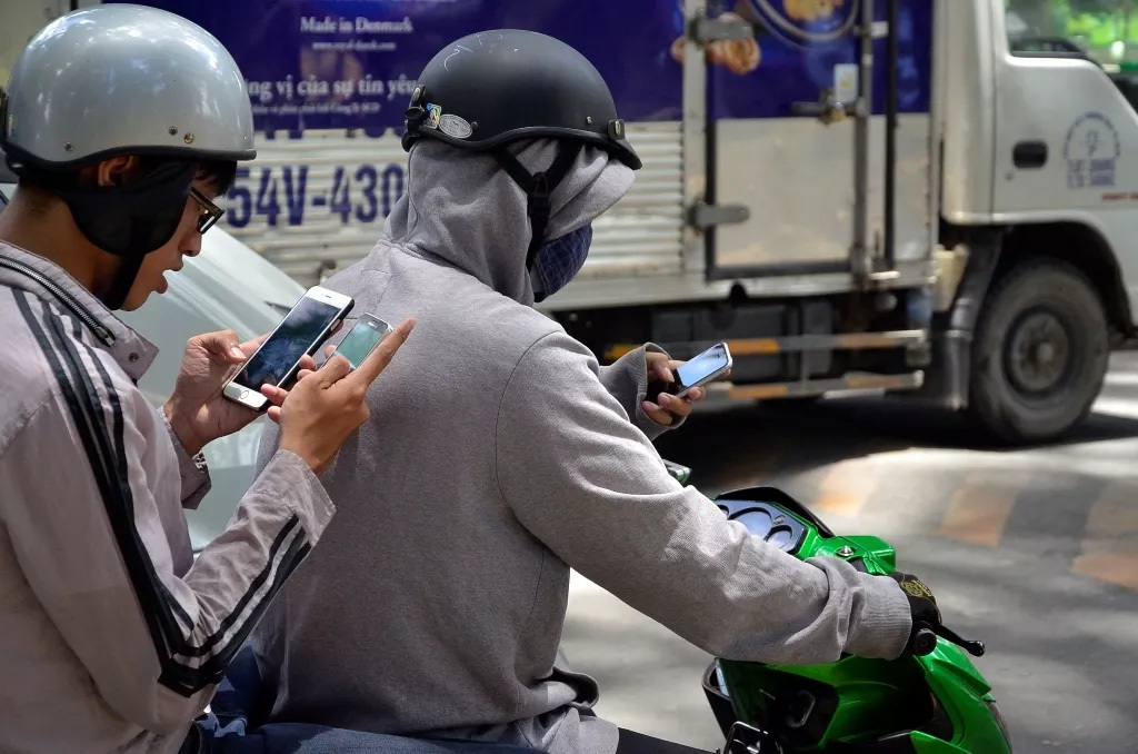 Người tham gia giao thông vừa đi xe vừa chơi Pokémon Go (Ảnh: Đình Thảo)
