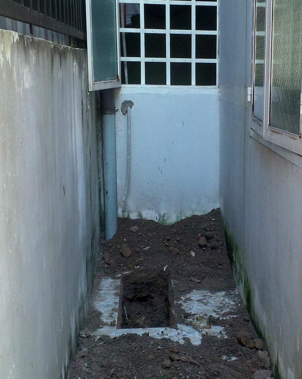 Hiện trường tên Tâm đào hố chôn xác con trai ngay sát bên hông nhà